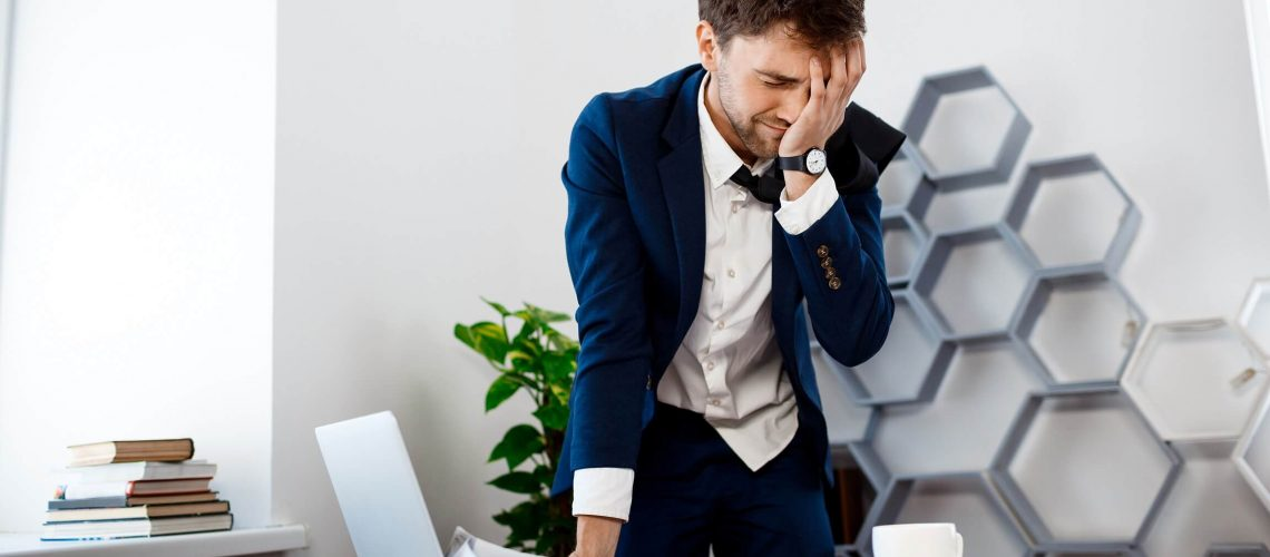 upset-young-businessman-standing-workplace-office-background